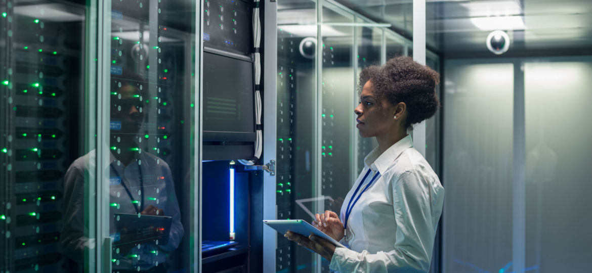 Female technician works on a tablet in a data center